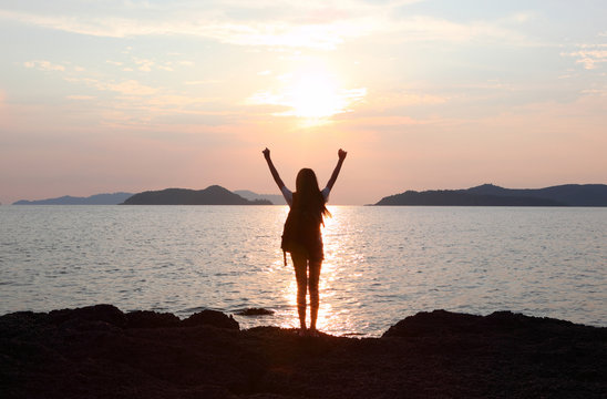 Free woman enjoying freedom feeling happy at beach at sunset. Beautiful serene relaxing woman in pure happiness and elated enjoyment with arms raised outstretched up. Asian Caucasian female model.