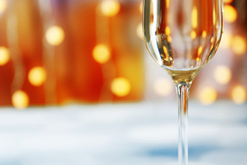 A glass of champagne on blurred lighted background