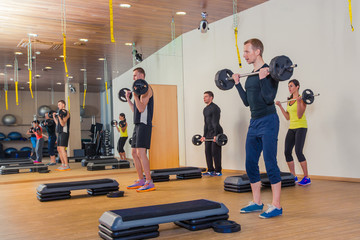 Sport, fitness, lifestyle and people concept - group flexing muscles with barbells in gym