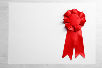 Award ribbon on white paper sheet, on wooden background