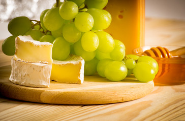 Still life of cheese, honey and grapes
