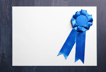 Award ribbon on white paper sheet, on wooden background