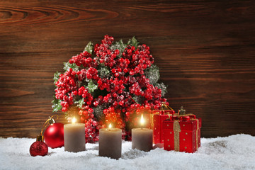 Three candles and toys with bouquet of holly berries in a snow over wooden background, still life