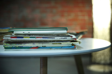 Pile of old books on the table against brick wall, close up