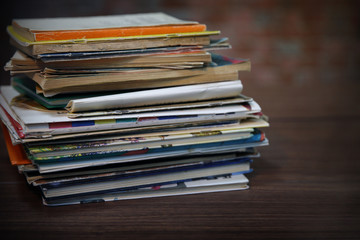 Pile of old books on wooden table against brick wall, close up