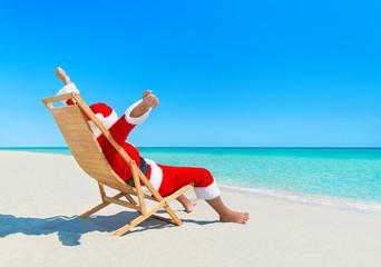 Christmas Santa Claus enjoy sun on deckchair at sandy beach