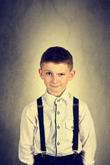 Funny emotionof  little boy young man with a raised eyebrow wearing costume with braces.Happy little boy over white background.Smiling, Happy, Joyful beautiful little boy , looking at camera.