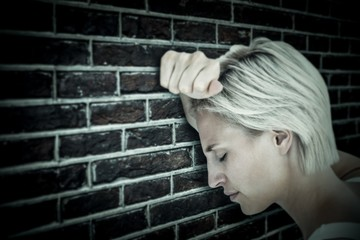 Composite image of sad blonde woman with her head on wall