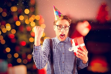 Composite image of geeky hipster wearing party hat holding gift