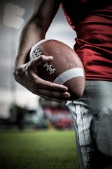 Composite image of sportsman holding american football ball