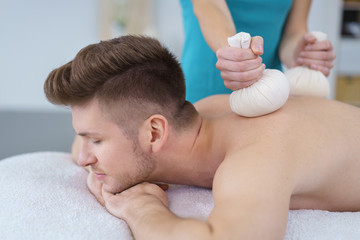 massage mit kräuterstempeln