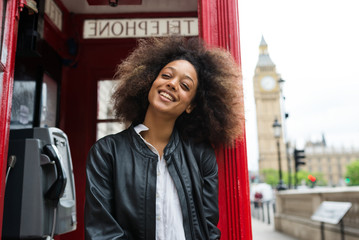 Smiling portrait of young woman close to red telephone box in London.