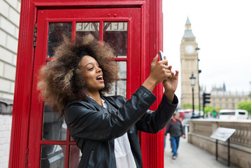 Young woman portrait close to red telephone box in London taking selfie.