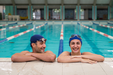 Young couple of swimmers inside swimming pool.