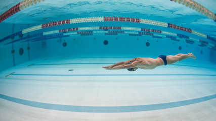 Professional man swimmer inside swimming pool. Underwater image.