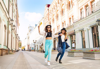 Two happily jumping girls while walking