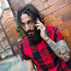 Young tattooed man talking at the phone in Shoreditch borough. London.
