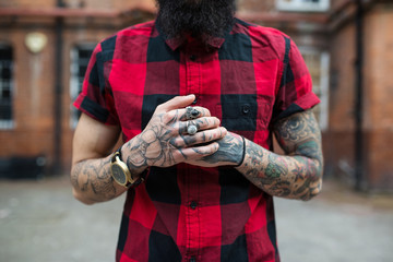 Hands close up of young tattooed man portrait in Shoreditch. London.