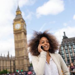 Young woman portrait in London on Westminster bridge talking at the phone.