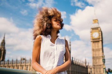 Young woman portrait in London on Westminster bridge with Big Ben in the background.