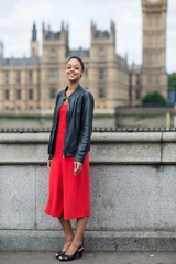 Young smiling businesswoman full body portrait outdoors in London.