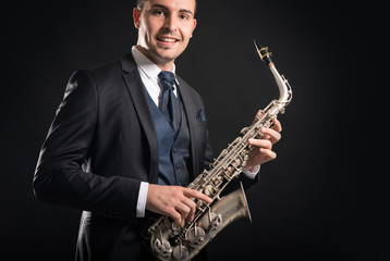 Saxophone player man isolated against black background. Close up