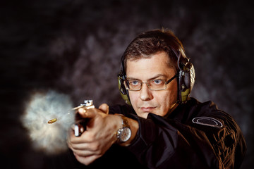 Closeup portrait of man with gun making shot at training club