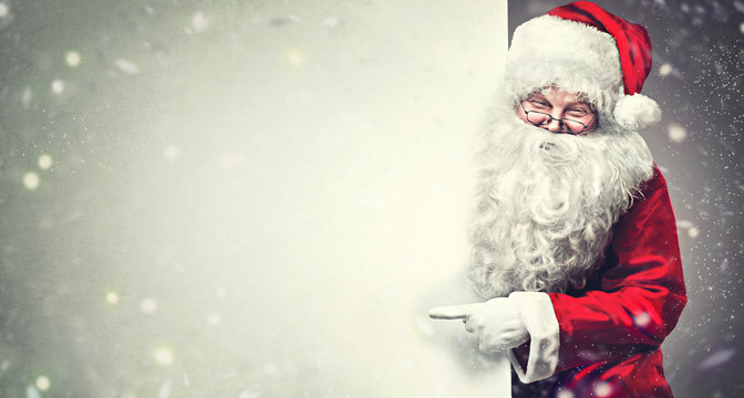 Smiling Santa Claus pointing on blank advertisement banner background with copy space