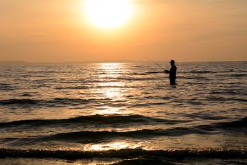 Silhouette angler sunset background.