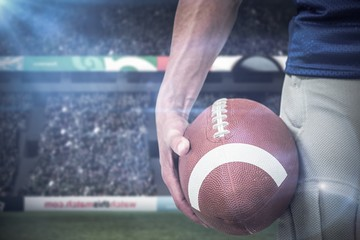 Composite image of midsection of sports player holding ball