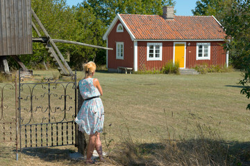 Attractive woman in summer dress leaning against a gate and looks over at an old, typical red wooden house on the island of Oland, Sweden. Summery scenery.