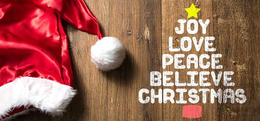 Joy Love Peace Believe Christmas written on wooden with Santa Hat