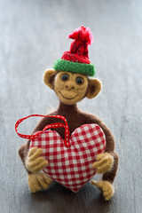 New Year 2016 the year of the monkey . Homemade toy monkey with a fabric heart on a brown wooden background .