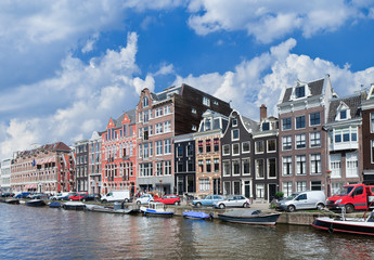 Canal with row of stately ancient mansions with parked cars and moored boats, Amsterdam, The Netherlands.
