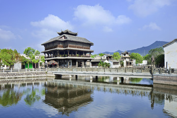 Ancient wooden house and bridge reflected in a tranquil canal, Hengdian, China