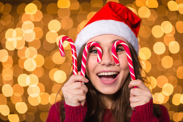 Amusing young female making funny face using christmas lollypops
