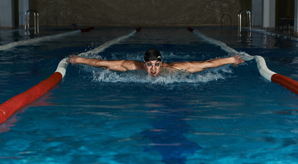 Male swimmer performing butterfly stroke in the pool. Young sportsman in swimwear exercising in the water.