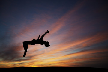 Wall Mural - silhouetted gymnast doing backflip in sunset sky