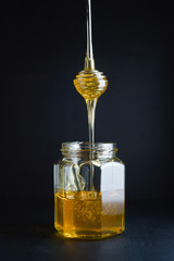 Honey flowing from metal honey dipper into a glass jar