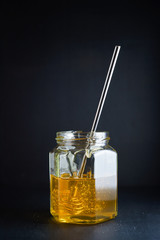 Glass jar with honey and metal honey dipper on dark background