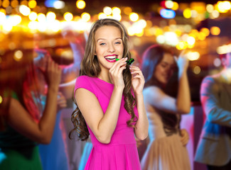 happy young woman or teen girl with party horn