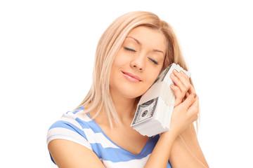 Woman sleeping on a stack of dollar bills