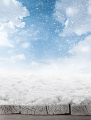 empty winter background of wooden table and sky with falling sno