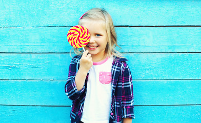 Happy smiling child with sweet lollipop having fun over colorful Wall mural