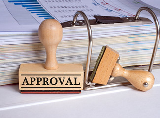 Approval rubber stamp with binder on desk in the office