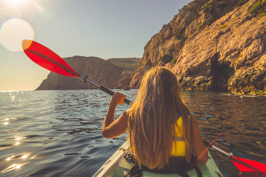 Young woman kayaking in the sea near mountains
