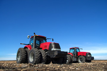 Fototapete - Two tractor cultivating the land