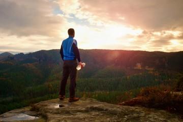 Sweaty tall hiker in cyan trikot with bottle of water. Adult tired tourist on the peak of rock watch into misty landscape.