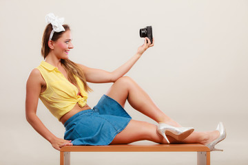 Pin up girl woman taking selfie photo with camera.