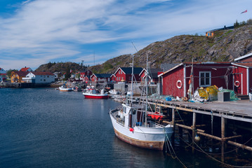 Fishermen houses on banks with boat
